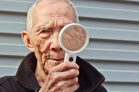 17861587 - the white hair old people who holding a magnifying glass