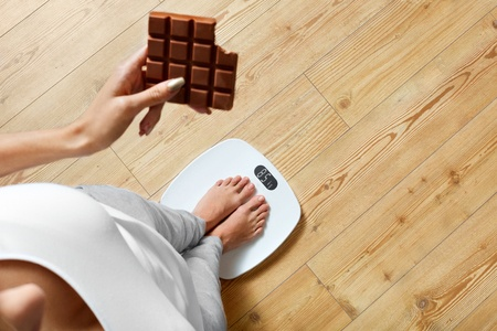 48712171 - diet. young woman standing on weighing scale and holding chocolate bar. sweets are unhealthy junk food. sugar is bad for health. dieting, healthy eating, lifestyle. weight loss. top view
