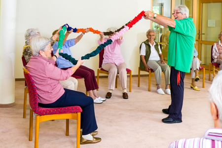 51693181 - enthusiastic physical therapist holding colorful garland up with group of senior women in fitness class at retirement home